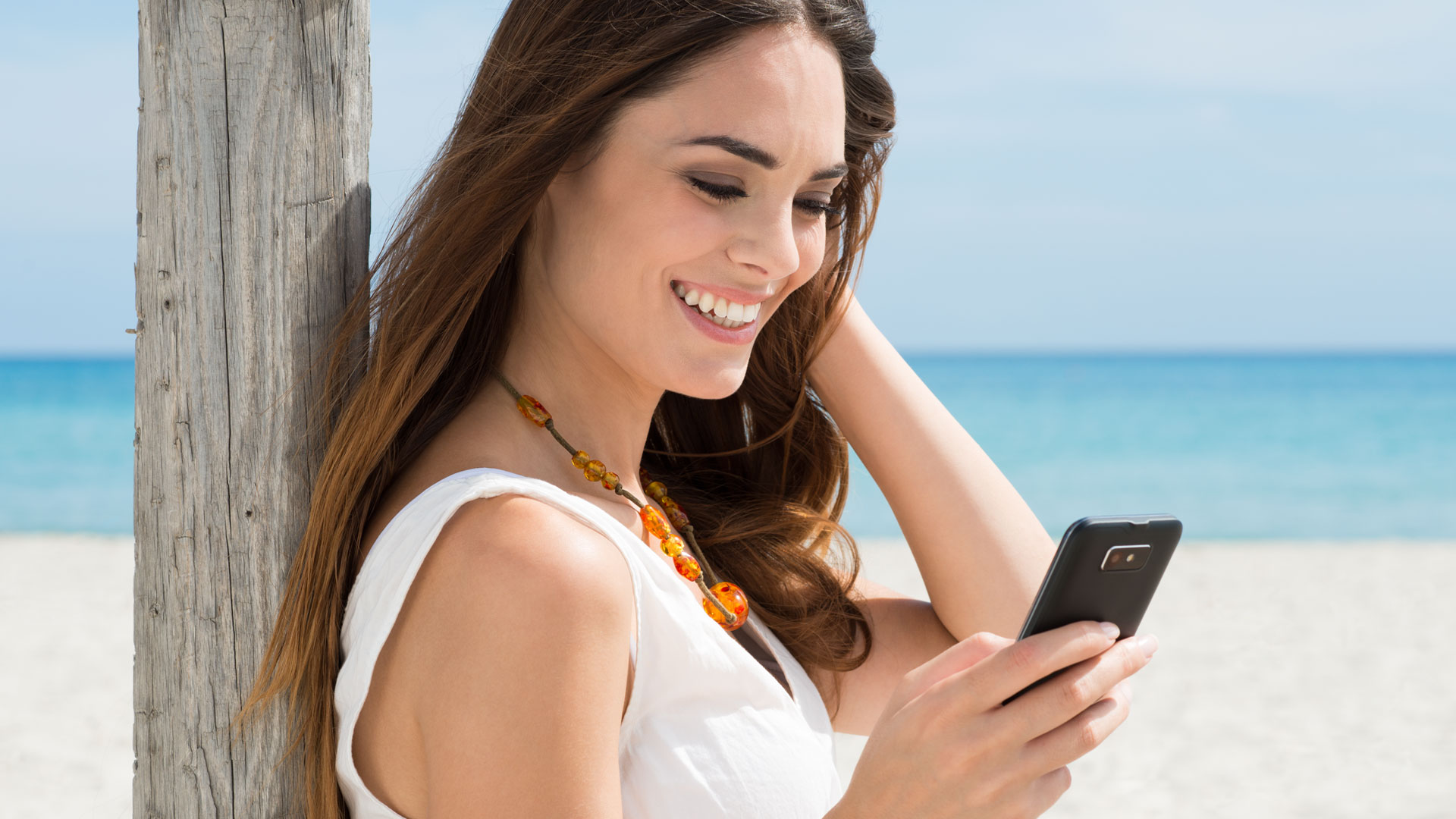 Slide - Woman smiling holding mobile phone